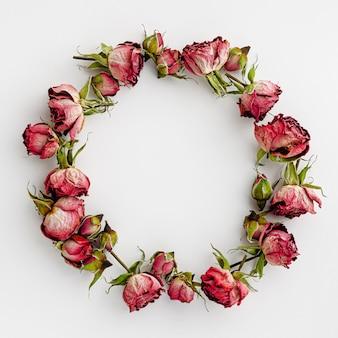 Cornice rotonda o corona fatta di rose rosse secche su bianco
