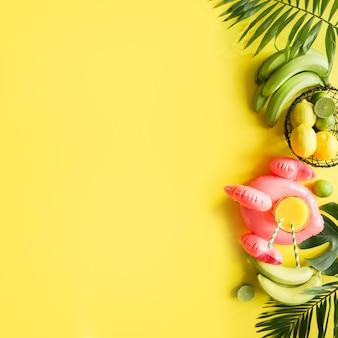 Cornice tropicale di frutta, banana, lime, foglie di palme, succo d'arancia in fenicottero rosa gonfiabile su sfondo giallo pastello incisivo.