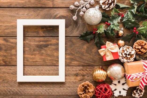 Cornice vicino a scatole regalo, rami verdi, ornamenti e palle di natale