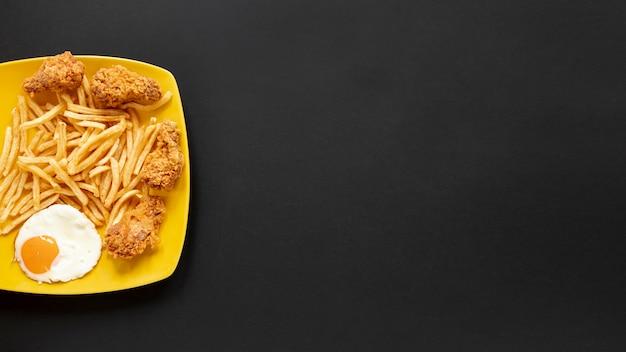Cornice vista dall'alto con patatine fritte e sfondo nero