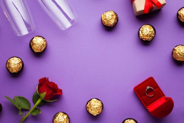 Cornice vista dall'alto con scatola di cioccolatini e anelli