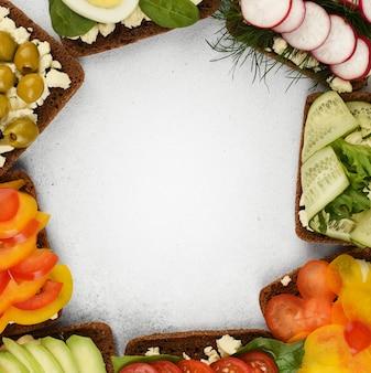 Cornice vista dall'alto di panini con verdure. panini affrontati aperti in tondo su fondo di pietra con spazio di copia.
