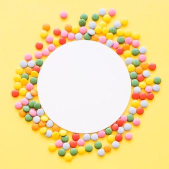 Cornice vuota bianca circondata da caramelle colorate gemme su sfondo giallo