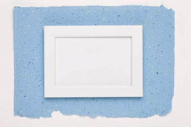 Cornice vuota bianca su carta blu su sfondo bianco