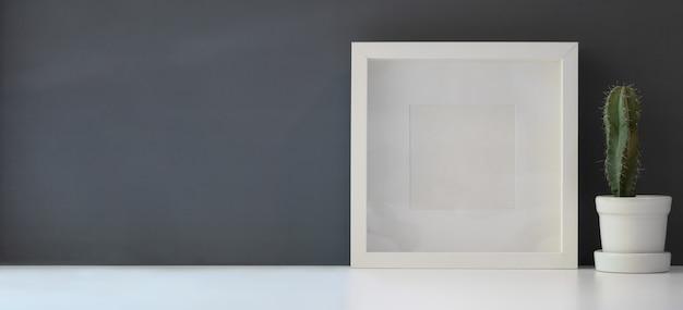 Cornice vuota con cactus in vaso in moderna area di lavoro sul tavolo bianco e parete grigio scuro