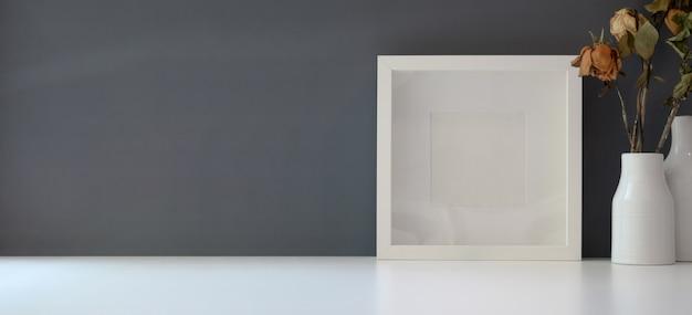 Cornice vuota con vaso di rose secche nell'area di lavoro moderna sul tavolo bianco e parete grigio scuro