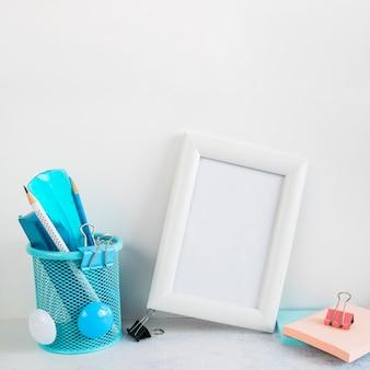 Cornice vuota e articoli di cancelleria sulla scrivania