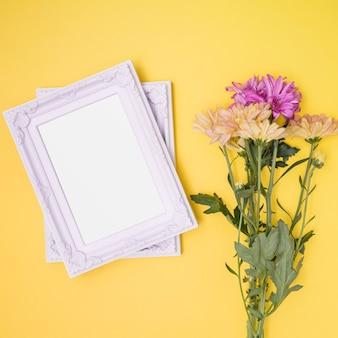 Cornici bianche accanto al mazzo di fiori