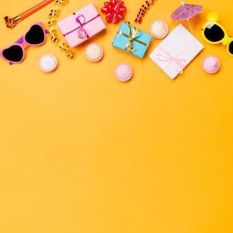 Corno di festa; occhiali da sole; filanti; scatole da regalo avvolte; e aalaw su sfondo giallo