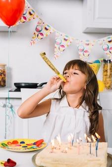 Corno di salto del partito della ragazza di compleanno che si siede dietro la torta di compleanno con le candele