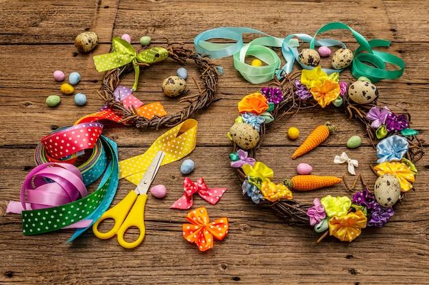 Corona artigianale in vimini pasquale con uova di quaglia e fiori fatti a mano. set di materiali e strumenti per il ricamo. resta a casa concetto. sfondo festivo di pasqua