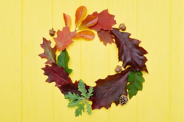 Corona delle foglie di autunno ed elementi di caduta con copyspace su giallo
