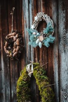 Corona di coni rustica festiva su un fondo di legno di marrone scuro. il concetto di vacanze di natale e capodanno.