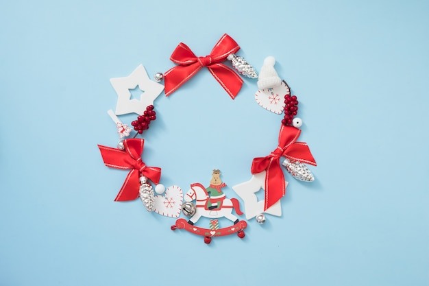 Corona di natale con decorazioni rosse e bianche su sfondo blu pastello. concetto di nuovo anno.