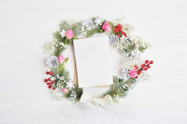 Corona di natale con foglio di carta decorato con bacche rosse, coni e rose
