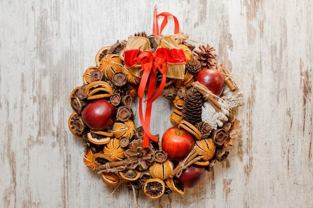 Corona di natale decorata con mele rosse, fette d'arancia essiccate, coni, bastoncini di cannella e fiocco