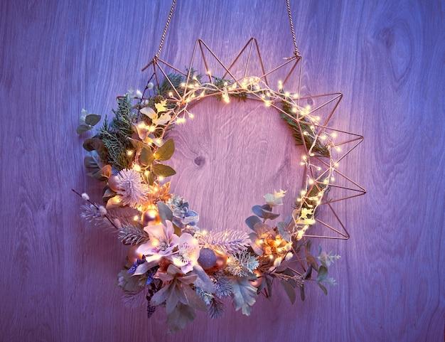 Corona di natale decorativo con abete, foglie di inverno e fiori con luci