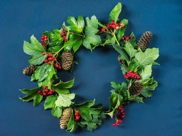 Corona di natale, ramo con bacche rosse, foglie verdi e coni di abete