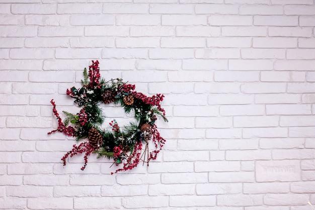 Corona di natale sul muro di mattoni bianco