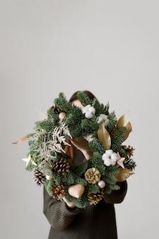 Corona di natale verde su mani femminili. minimo sulla superficie bianca. decorazione stagionale. copia spazio