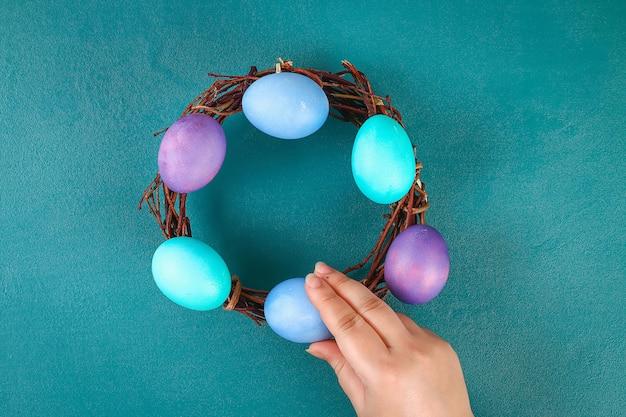 Corona di pasqua fai-da-te di ramoscelli, uova dipinte e fiori artificiali su uno sfondo verde.