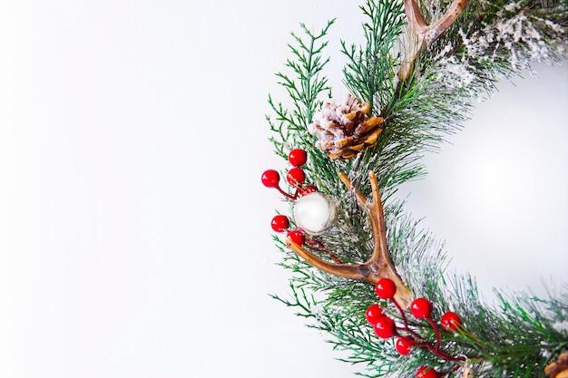 Corona piacevole di natale con le bacche e il pinecone rossi su priorità bassa bianca. decorazioni per la casa di natale. biglietto di auguri di capodanno. buon natale e felice anno nuovo family holiday festival concept, piatto laici