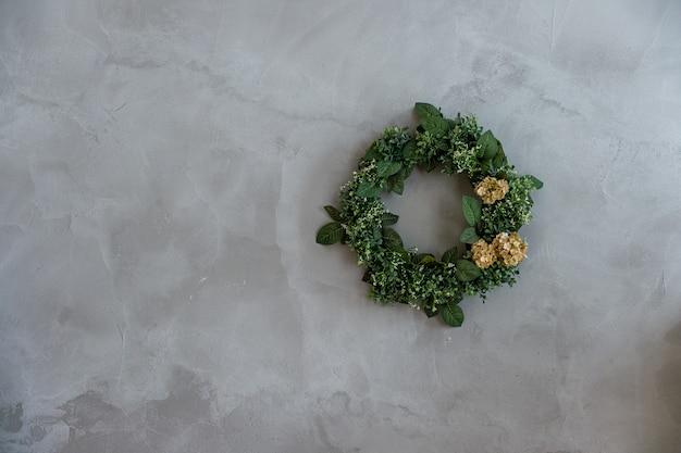 Corona verde rotonda dei fiori asciutti che appendono sulla parete