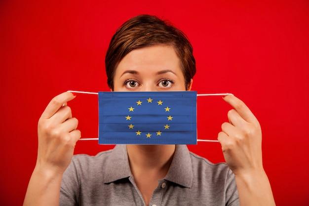 Coronavirus covid-19 in europa. donna in maschera protettiva medica con l'immagine della bandiera dell'europa.