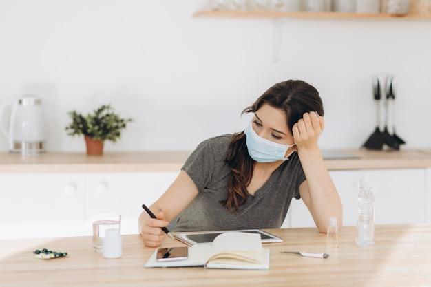 Coronavirus. giovane donna d'affari, lavorando da casa indossando maschera protettiva. ragazza in quarantena per coronavirus che indossa una maschera protettiva. lavorare da casa con gel disinfettante e acqua