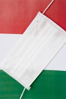 Coronavirus in italia. maschera antibatterica medica sullo sfondo della bandiera italiana