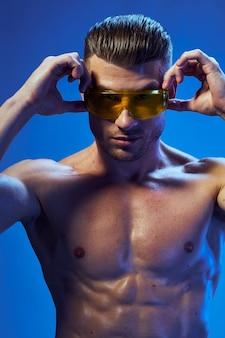 Corpo atletico bello dell'uomo con i muscoli che posano con gli occhiali da sole