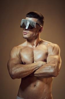 Corpo atletico bello dell'uomo con la posa dei muscoli