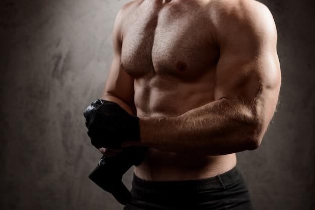 Corpo di uomo sportivo sopra il muro scuro.
