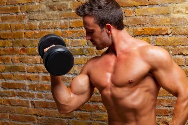Corpo muscoloso uomo con pesi sul muro di mattoni