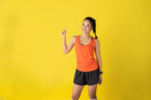 Corridore asiatico femminile che posa in abiti sportivi