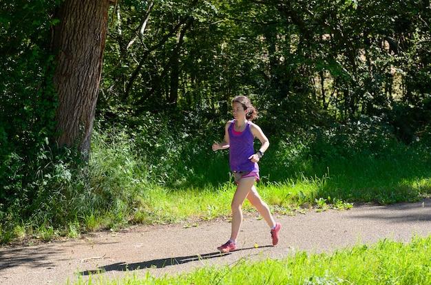 Corridore attivo della donna che pareggia vicino al fiume del canale, correndo all'aperto, sport, forma fisica e concetto sano di stile di vita