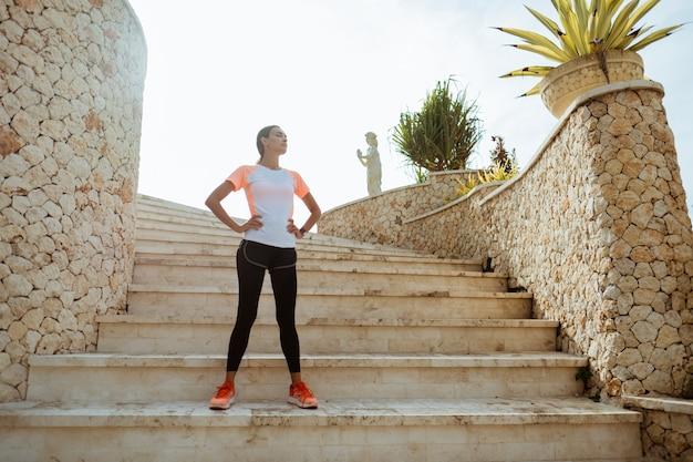 Corridore attraente prendendo pausa dopo il jogging all'aperto