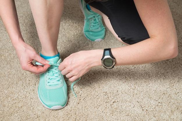 Corridore che allaccia i lacci indossando monitor della frequenza cardiaca e tracker di attività per esercizi cardio