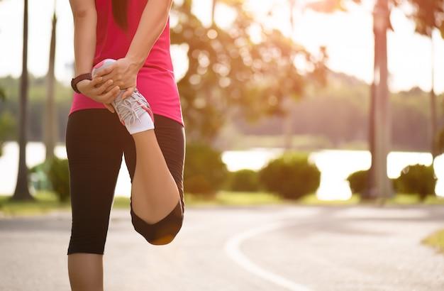 Corridore che allunga le gambe prima di correre nel parco. concetto di esercizio all'aperto.