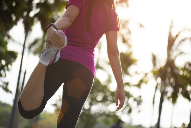 Corridore della donna che allunga le gambe prima della corsa. attività di esercizio all'aperto.