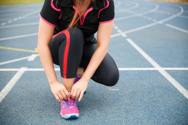 Corridore della donna che lega le scarpe da corsa prima dell'esecuzione per l'esercizio di mattina. corridore della donna che controlla scarpa per prepararsi a correre.