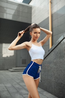 Corridore della donna di forma fisica che si rilassa dopo la città che funziona e che risolve all'aperto.