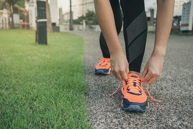 Corridore della giovane donna che lega le scarpe da corsa nel parco all'aperto