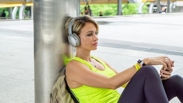 Corridore di forma fisica che ascolta la musica con gli auricolari per la motivazione che si distende sedendosi ricevendo i