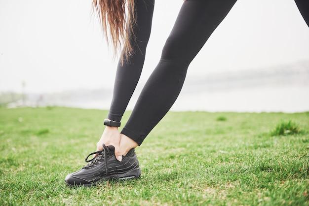 Corridore di giovane donna fitness allungando le gambe prima di correre sul parco