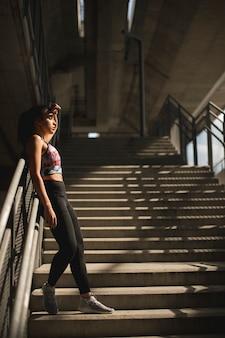 Corridore femminile abbastanza giovane che riposa sulle scale