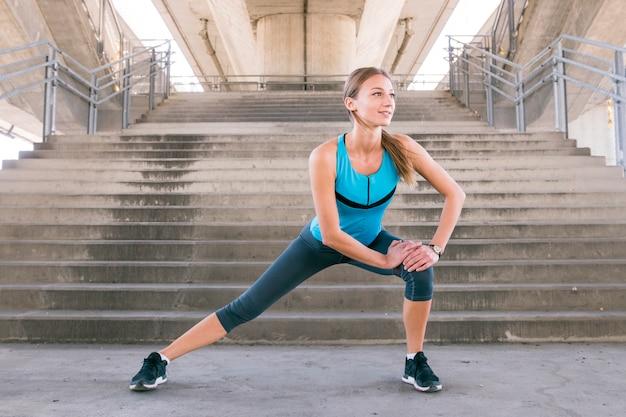 Corridore femminile di giovane forma che allunga le gambe prima di correre