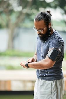 Corridore indiano che controlla tempo