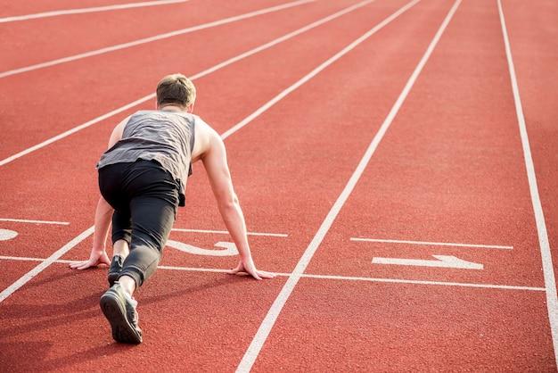 Corridore maschio che inizia lo sprint dalla linea di partenza