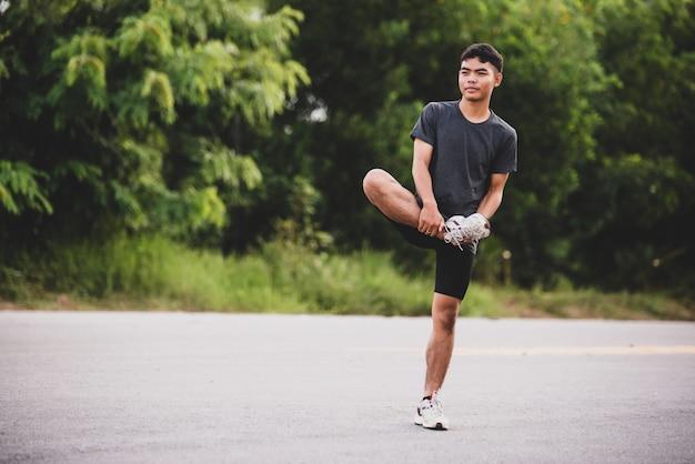 Corridore maschio facendo esercizio di stretching, preparando per allenamento